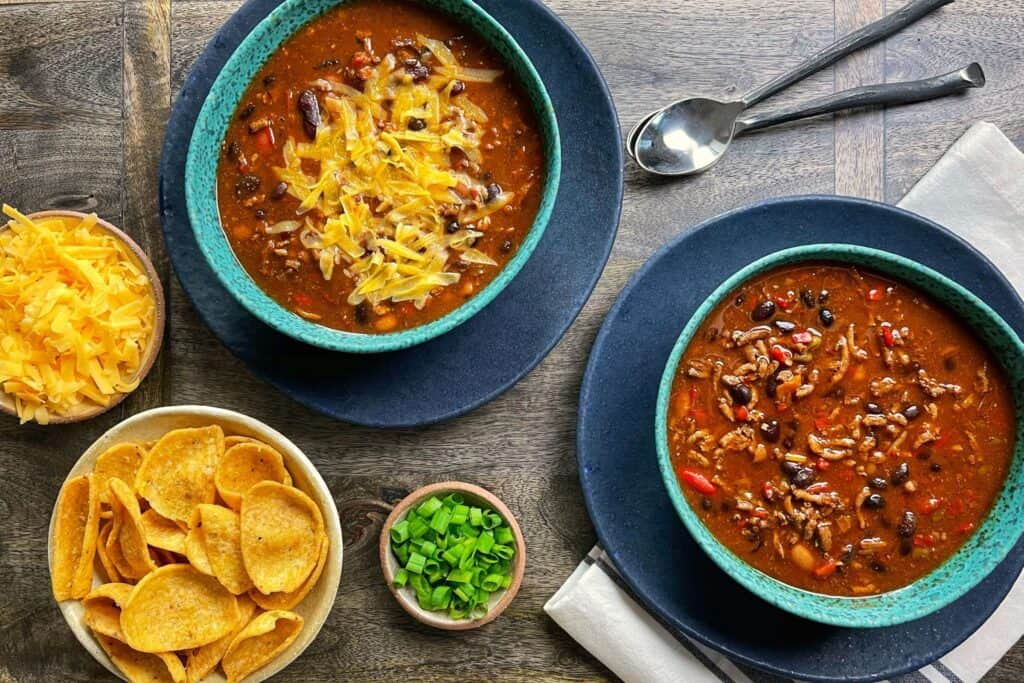 two bowls of turkey chili with corn chips, scallions, and shredded cheese