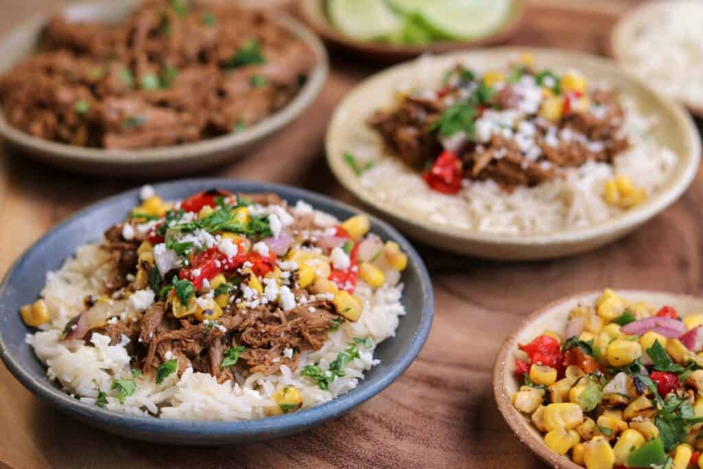 barbacoa beef burrito bowls with rice and roasted corn salsa