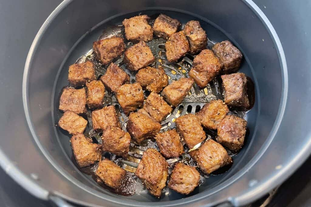 cooked steak bites in the air fryer basket