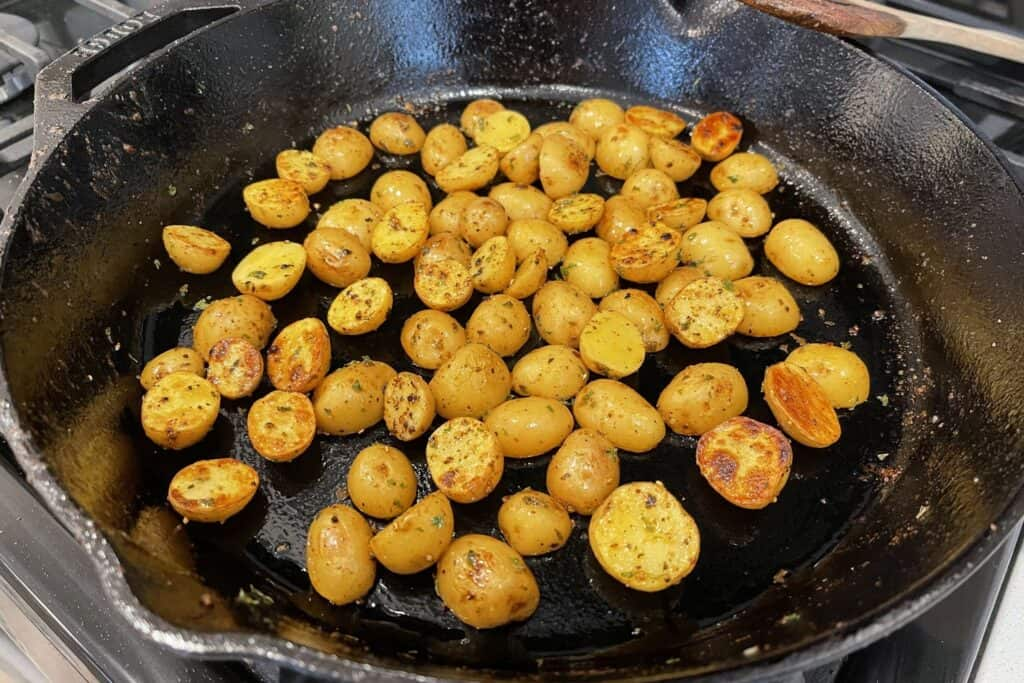halved baby gold potatoes in a cast iron skillet