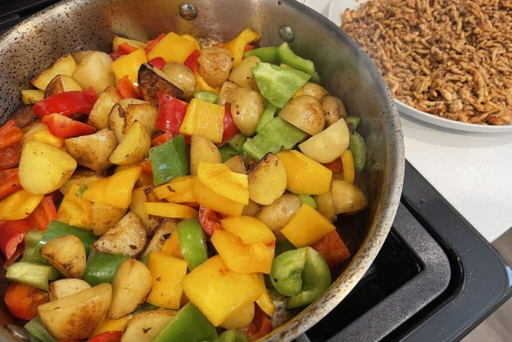 breakfast potatoes and peppers in the sauté pan