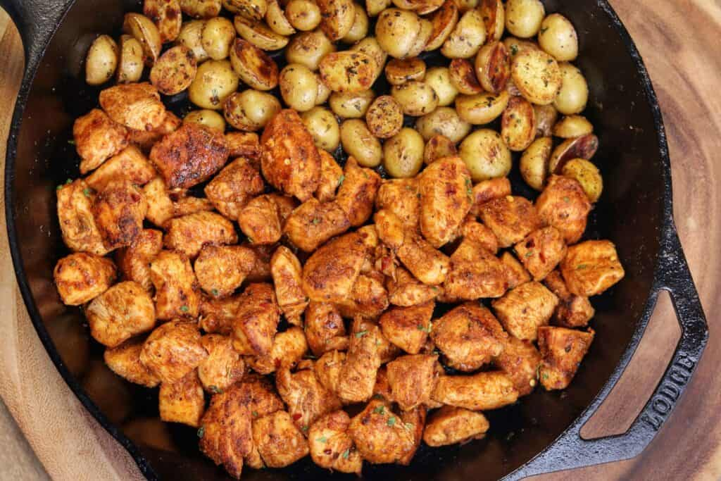 buffalo chicken bites and crispy gold potatoes in a cast iron skillet