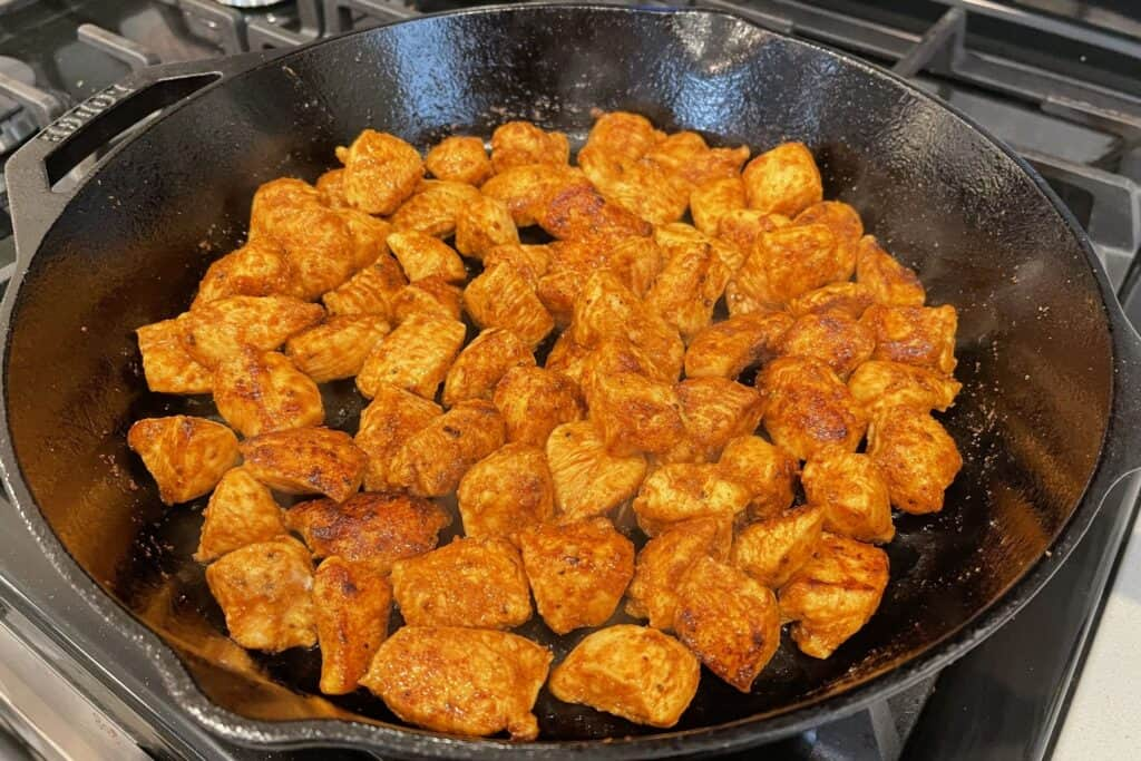 cooked buffalo chicken bites in a cast iron skillet