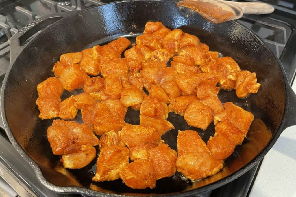 cooking the chicken bites in a cast iron skillet
