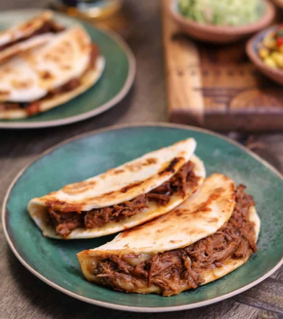 two cheesy grilled tacos with barbacoa beef