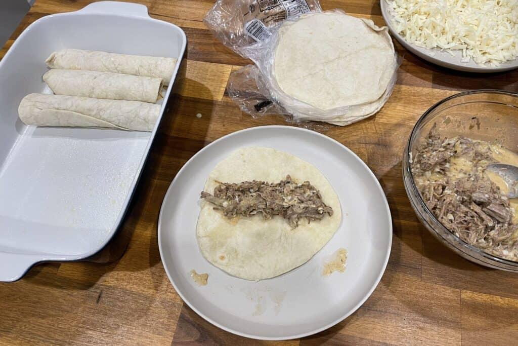 assembling the barbacoa beef enchiladas