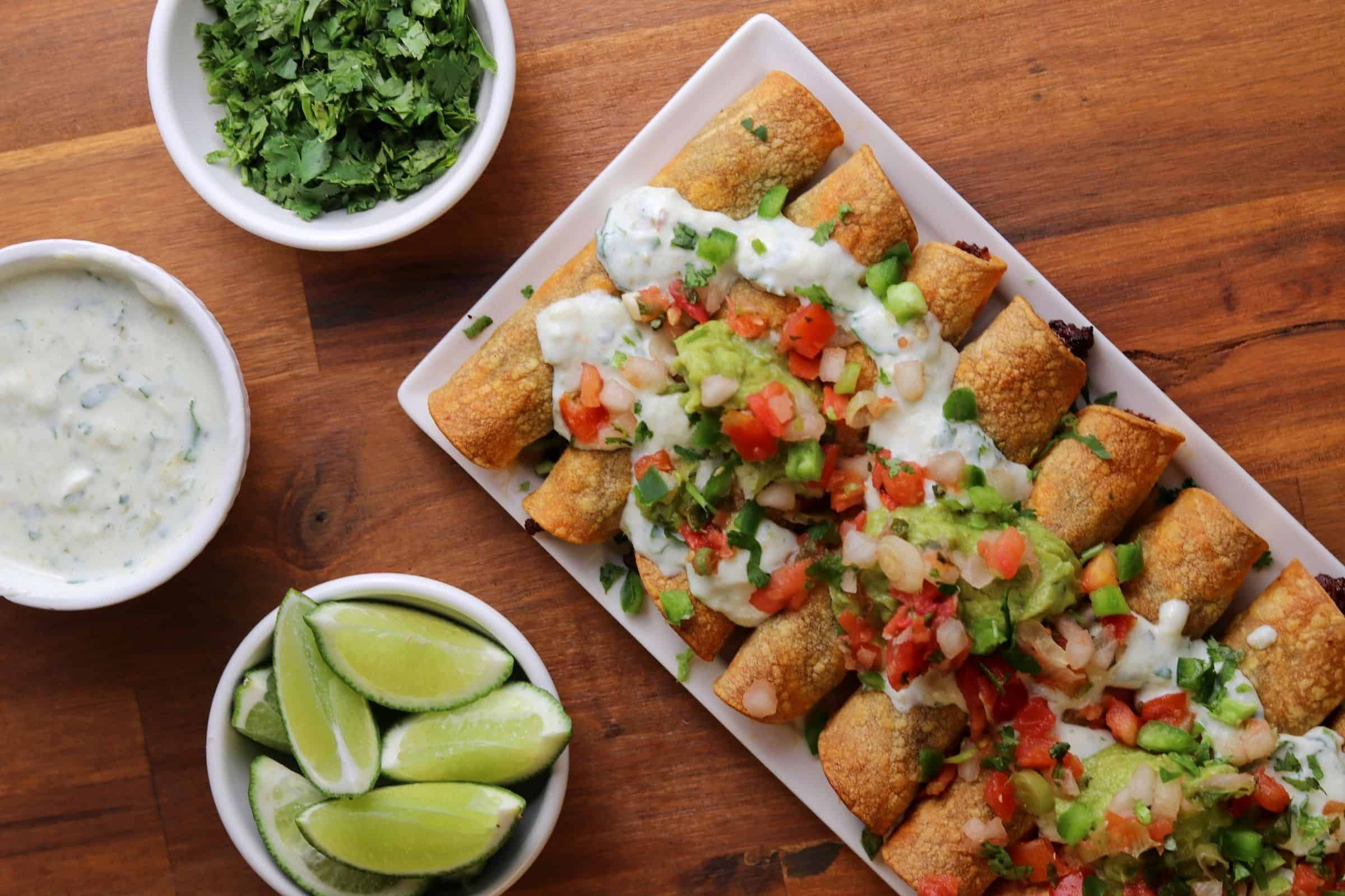 a white plate with baked taquitos topped with guacamole, fat free Greek yogurt, cilantro, and pico de gallo