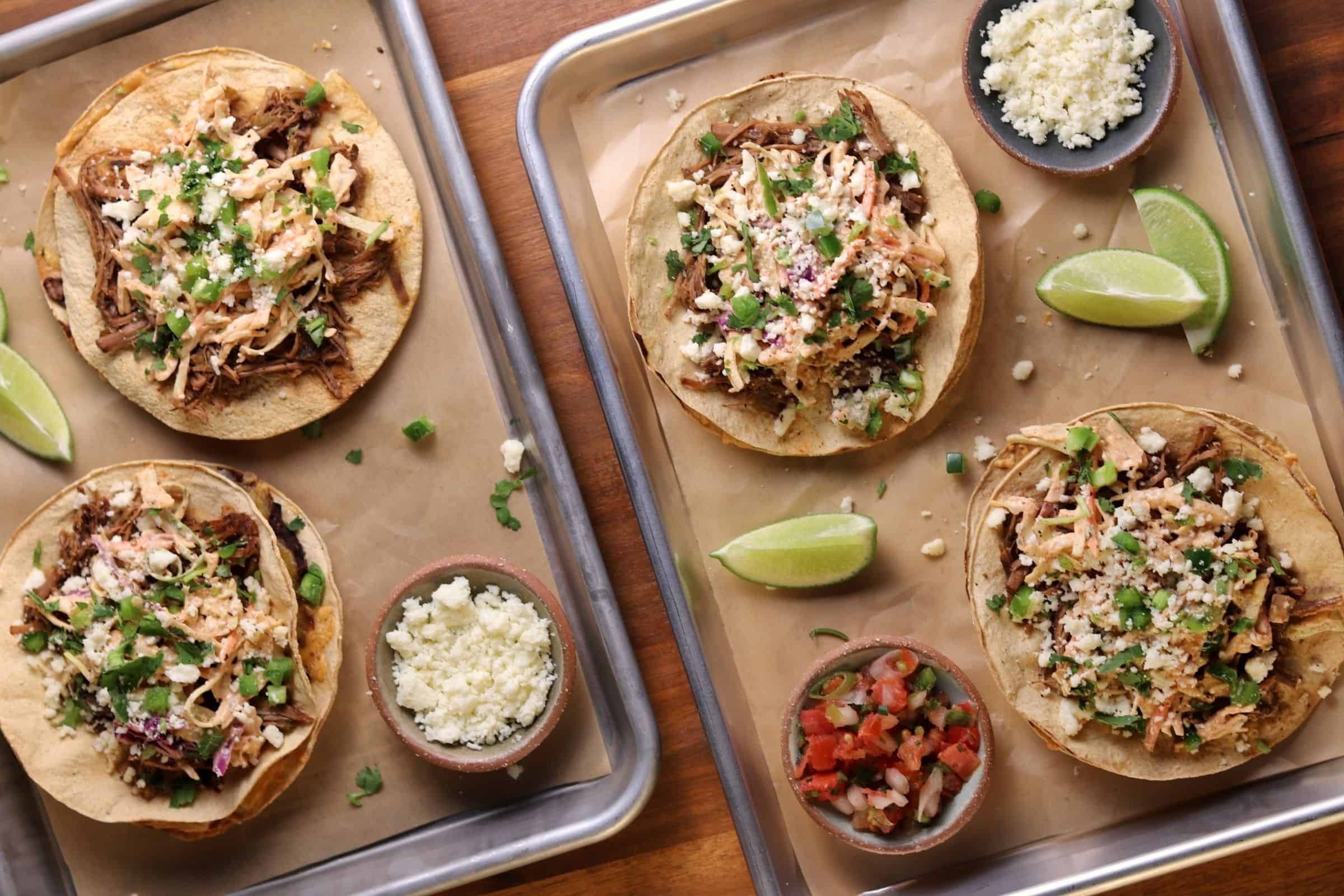 four beef tostadas with slaw on quarter sheet pans with queso fresco, pico, and lime wedges