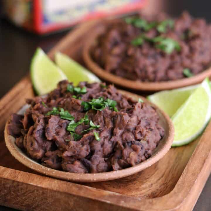 a bowl of refried black beans on a wooden serving plate with lime wedges