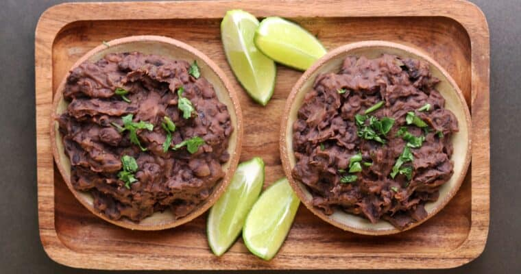 two bowls of refried black beans with lime wedges and cilantro