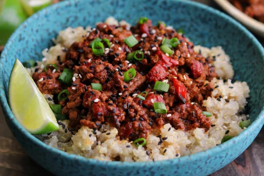 spicy sesame ground beef in a bowl with quinoa, green onion, sesame seeds, and a lime wedge
