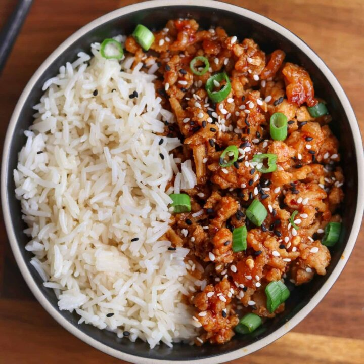 black bowl with rice and firecracker ground chicken topped with green onion and toasted sesame seeds