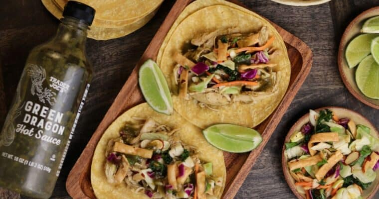 two tacos with chicken and Asian slaw on a wooden plate