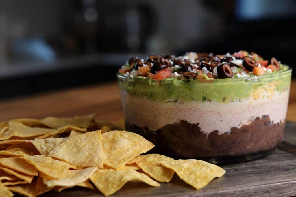 bowl of layer dip on a board with tortilla chips