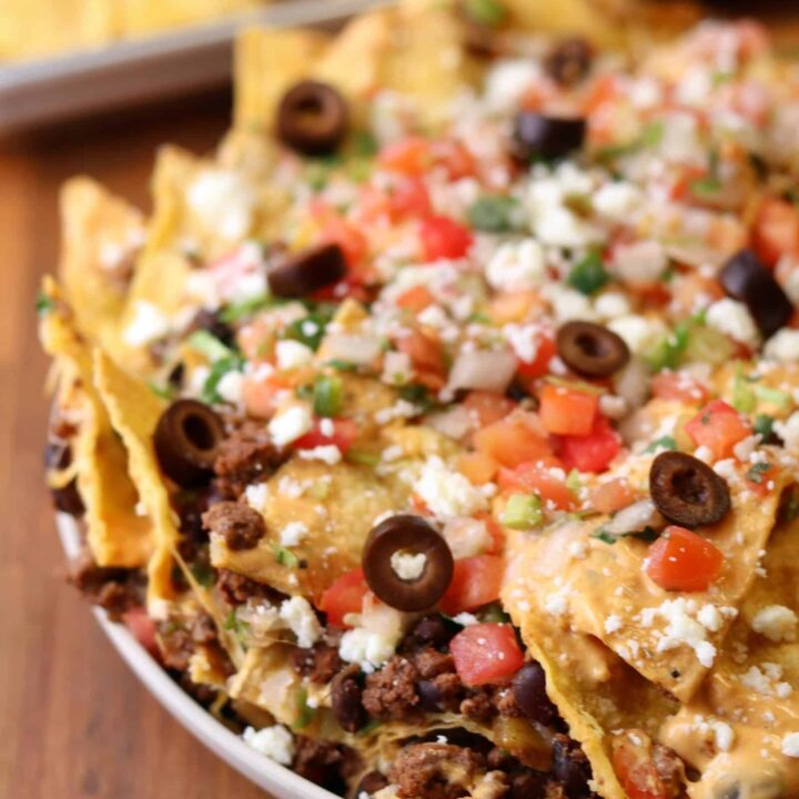 trash can nachos copycat on a plate with olives, pico de gallo, and queso fresco on top