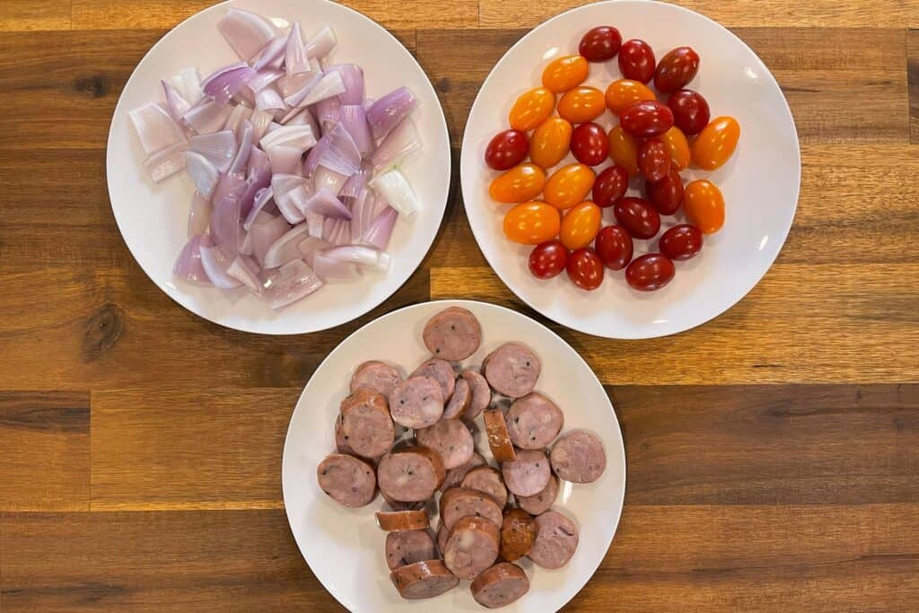 three plates with shallots, tomatoes, and sliced rounds of chicken sausage