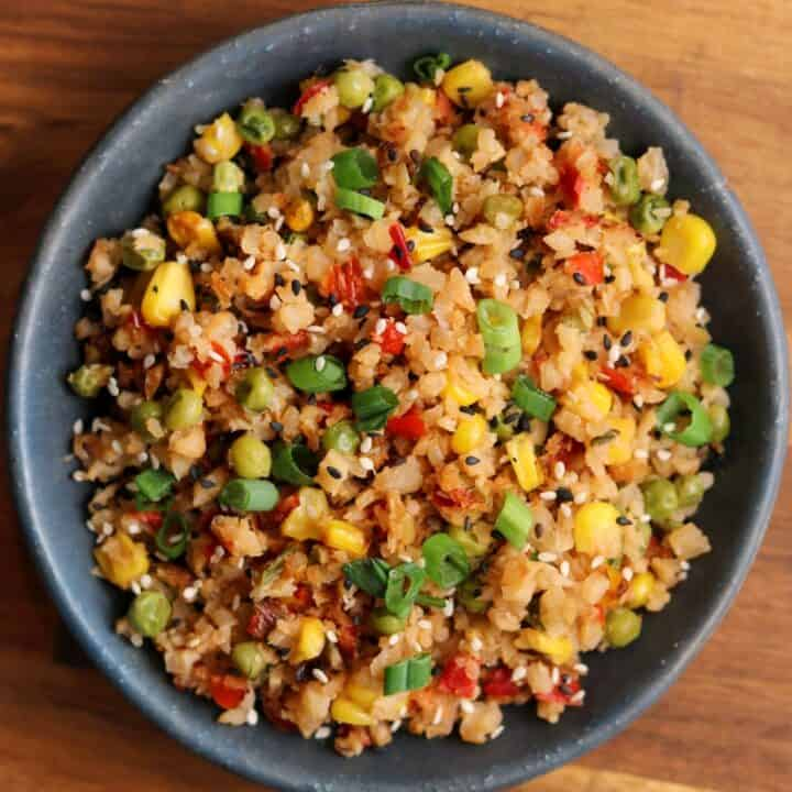 fried cauliflower rice with green onion and sesame seeds in a bowl