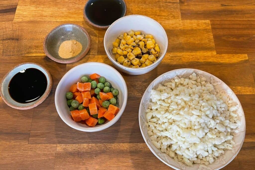 toasted sesame oil and soy sauce with frozen cauliflower rice, carrots, corn, and peas