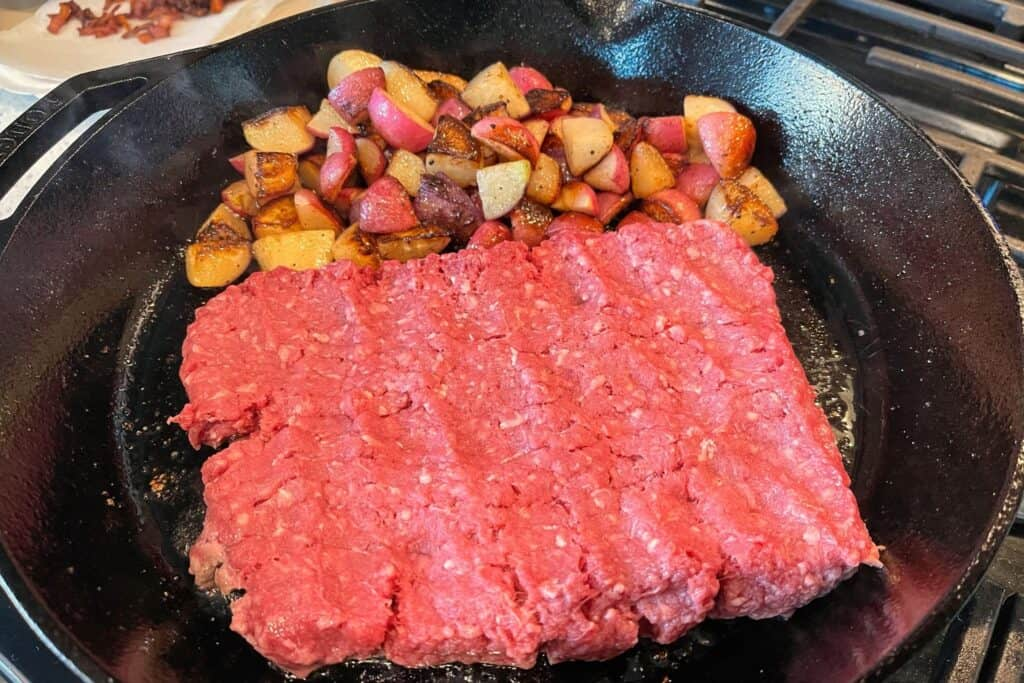 one pound of ground beef in a cast iron skillet with sautéed radishes pushed to one side
