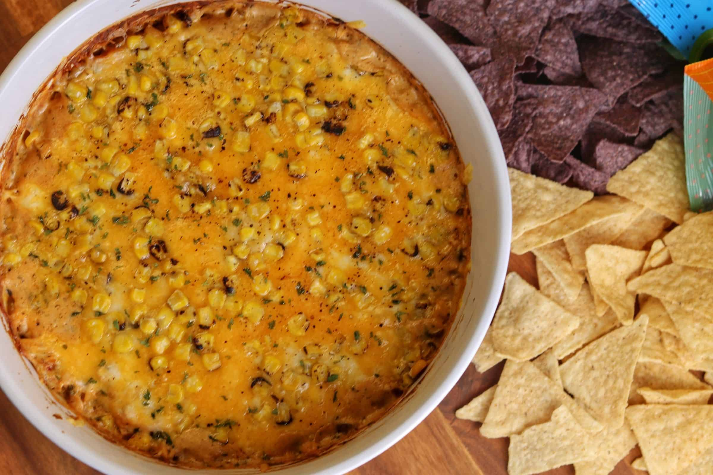 large bowl of chicken dip with two types of tortilla chips beside the bowl