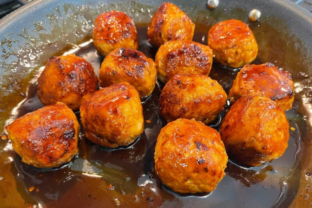 finished firecracker sauce on cooked meatballs