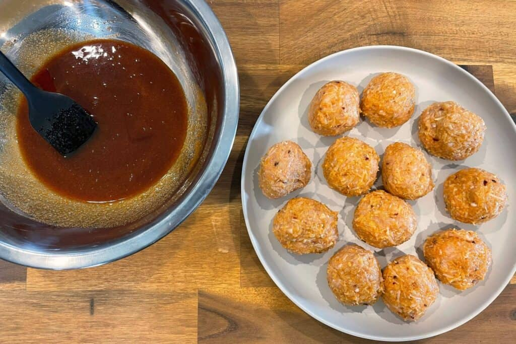 formed chicken meatballs on a plate with a bowl of firecracker sauce