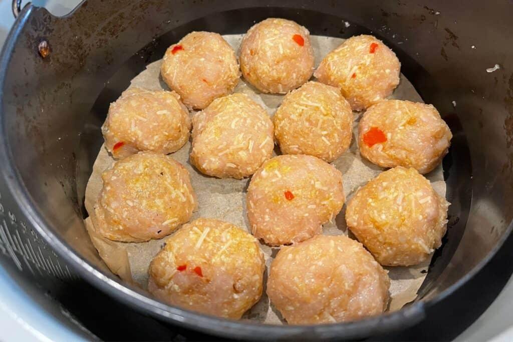 chicken meatballs in an air fryer basket