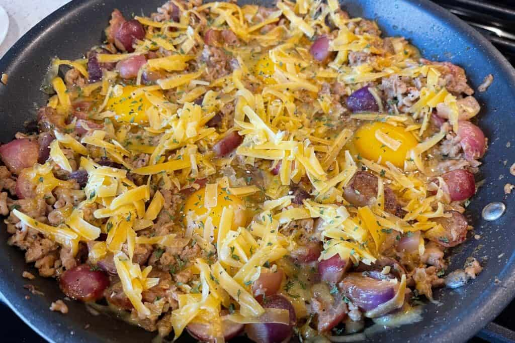 eggs and shredded cheddar added to the skillet