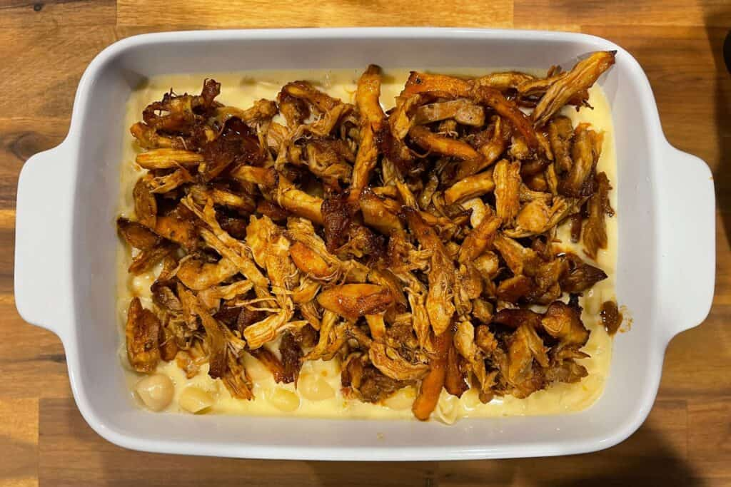 pulled chicken added to the mac and cheese in a baking dish