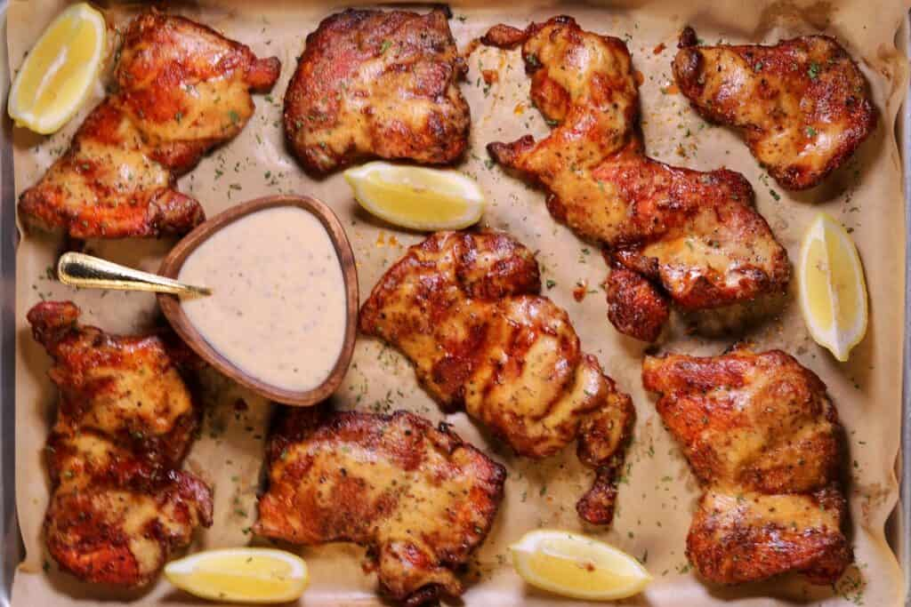 smoked chicken thighs on a baking sheet with Alabama white sauce and lemon wedges