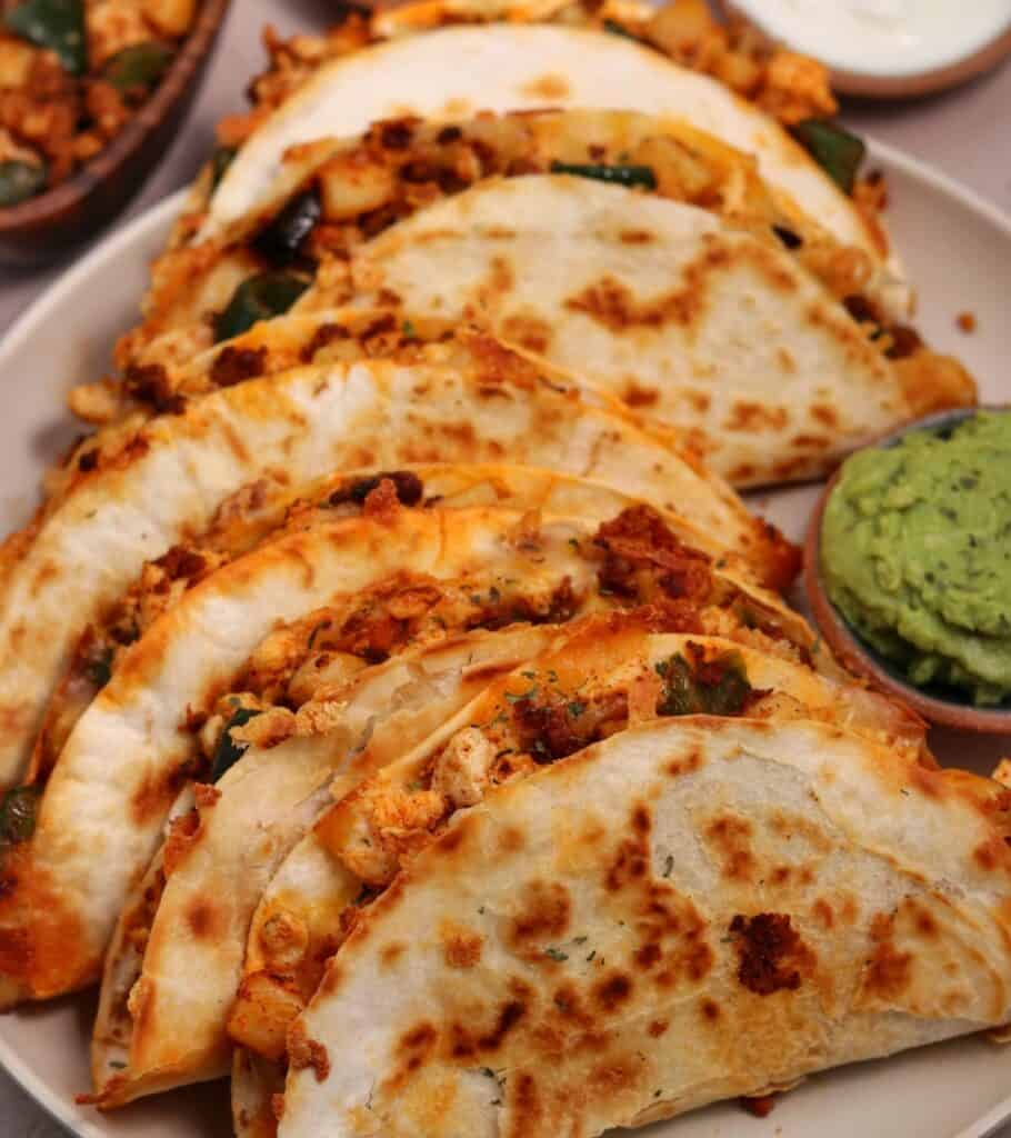5 breakfast quesadillas on a plate with a small bowl of guacamole