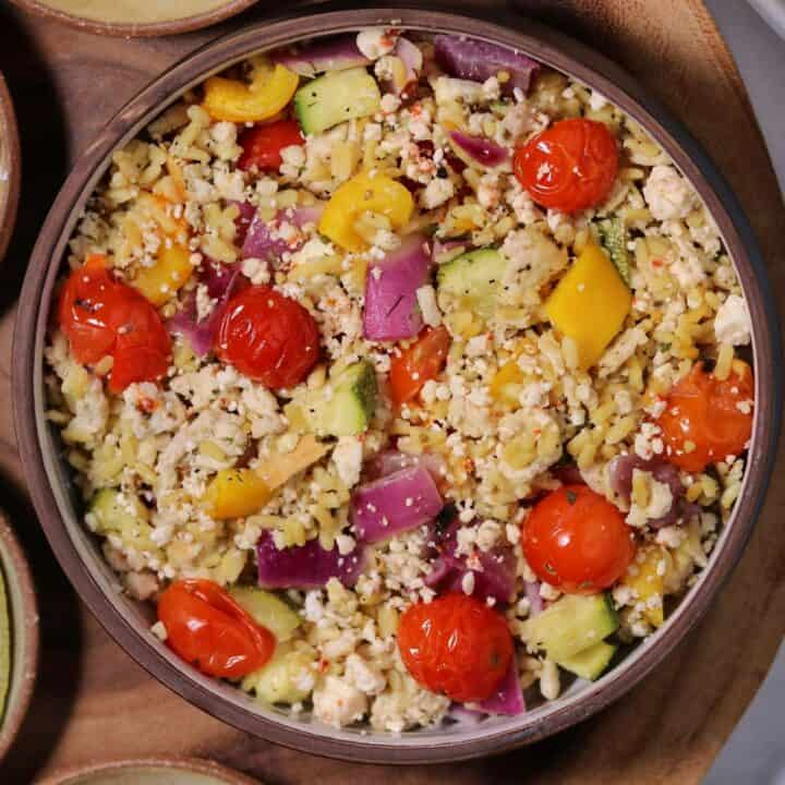Greek ground chicken and rice with roasted vegetables in a bowl