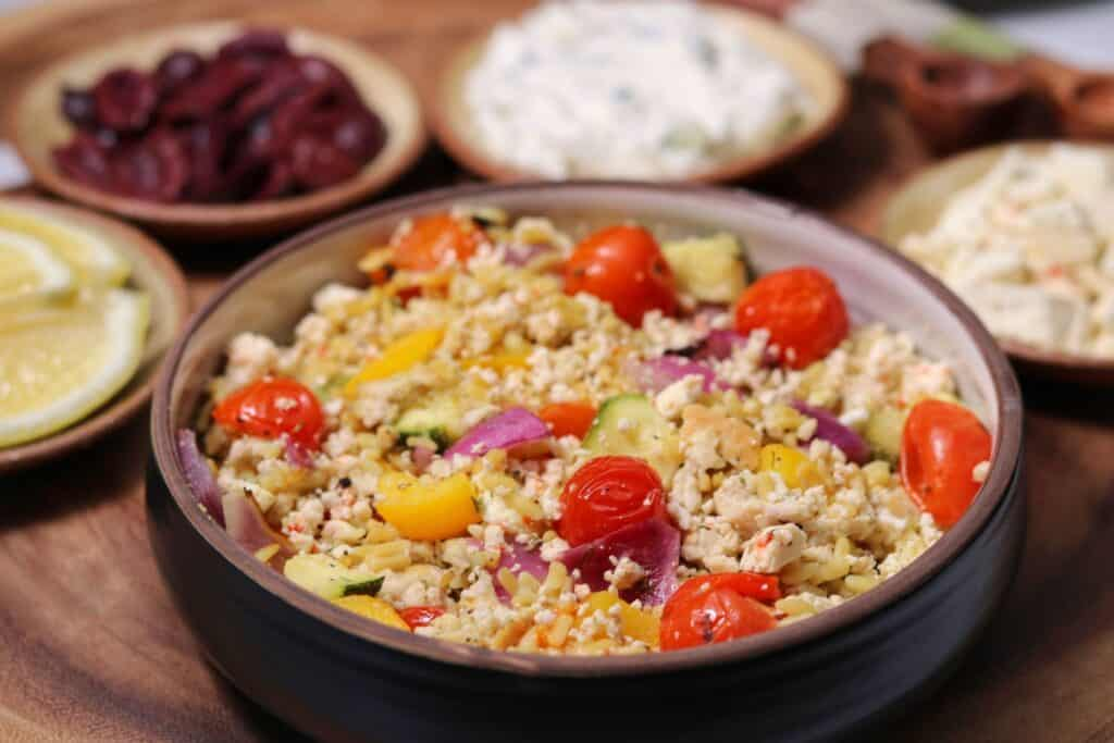 a Greek chicken bowl with sides of Tzatziki sauce, Kalamata olives, feta cheese, and lemon wedges