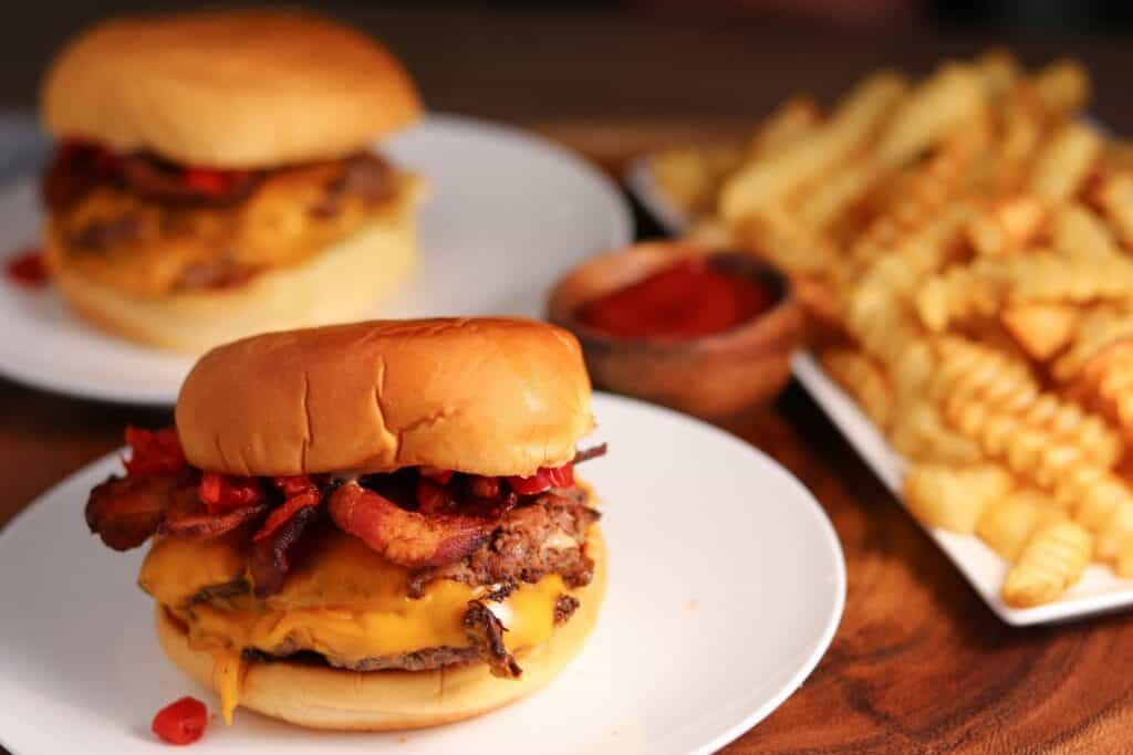 two smokeshack burgers on plates beside crinkle cut fries and ketchup
