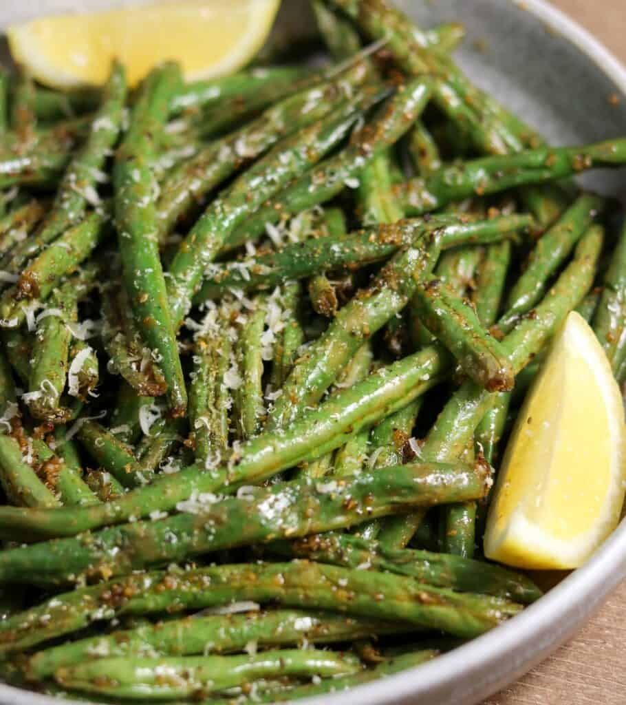 air fryer green beans in a bowl with grated parmesan and lemon wedges