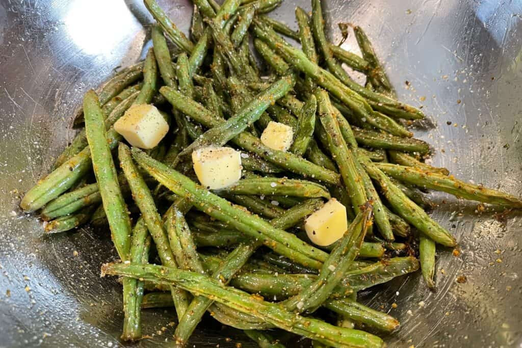 air fryer green beans back in the mixing bowl with butter, salt, and pepper