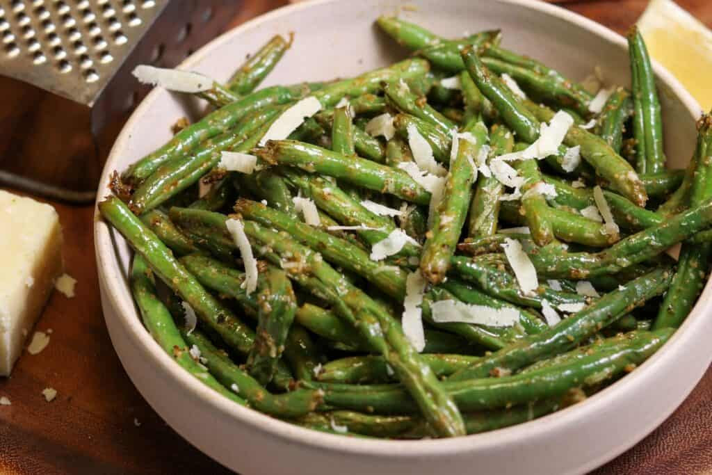green beans in a bowl with grated parmesan and a lemon wedge