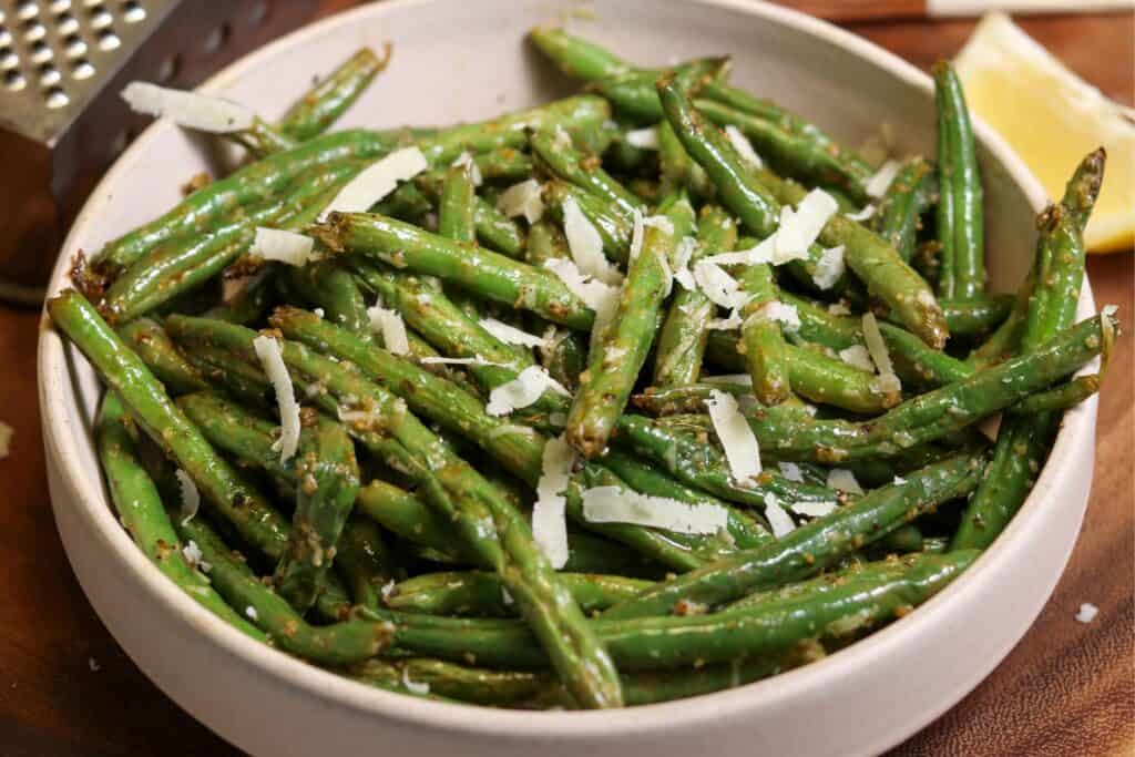final air fried green beans in a bowl with grated parmesan and lemon juice