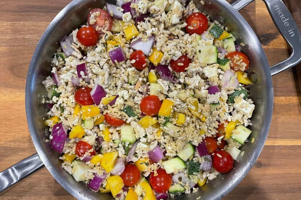 ground chicken and rice with Greek vegetables mixed in the skillet