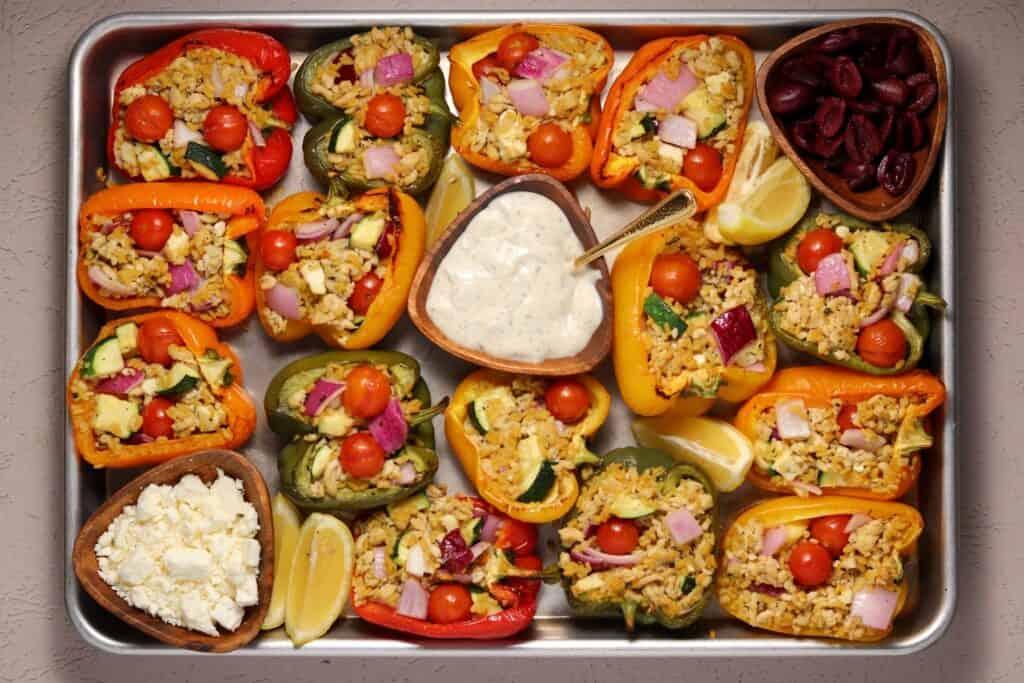 Greek stuffed peppers on a sheet pan with Tzatziki sauce, feta, lemon wedges, and Kalamata olives