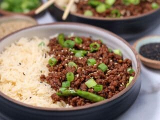 Mongolian ground beef in a bowl with basmati rice, green onion, and toasted sesame seeds