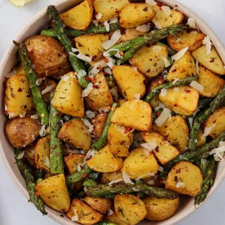 air fryer asparagus and potatoes in a bowl with grated parmesan and lemon