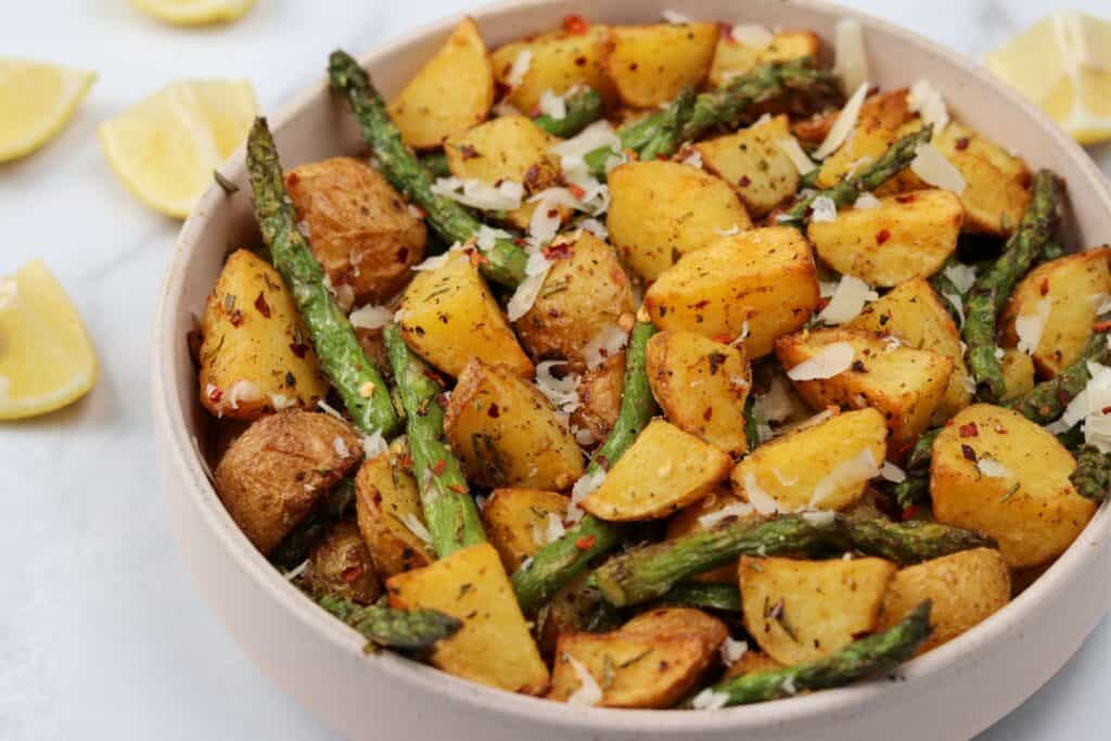 air fried asparagus and potatoes in a bowl with parmesan and lemon wedges