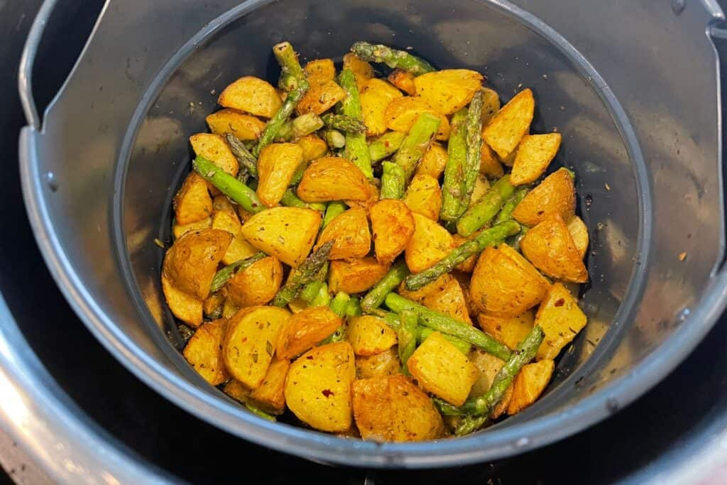 seasoned asparagus and air fried potatoes in the air fryer basket