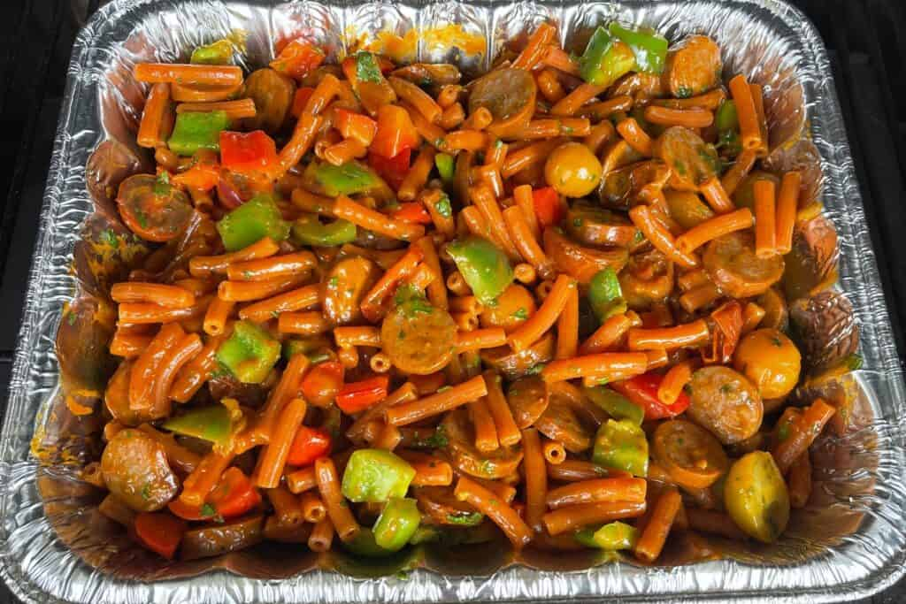smoked cajun sausage and veggies with alfredo and cooked pasta added to the pan
