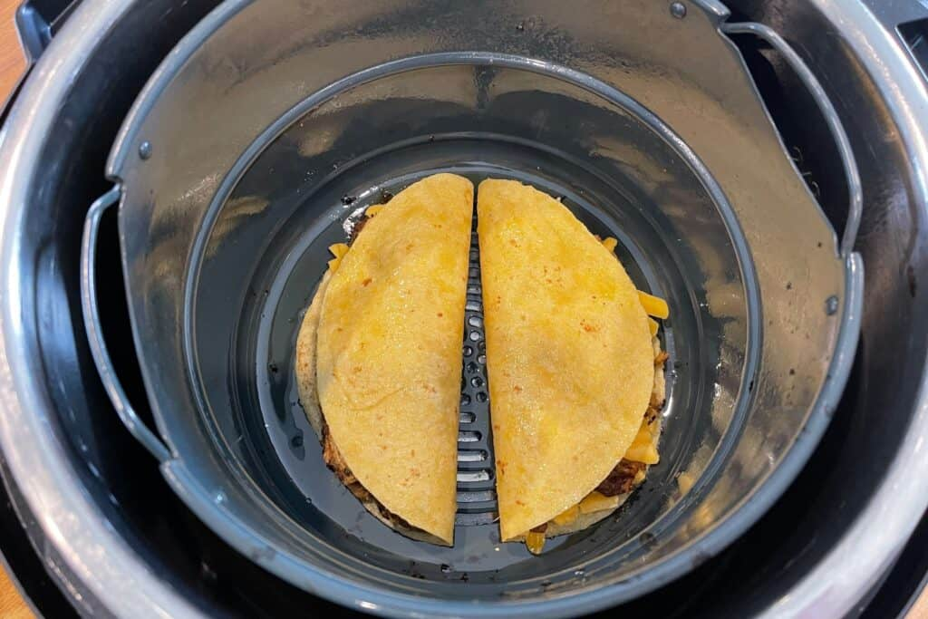 two quesadillas in the Instant Pot air fryer basket before cooking