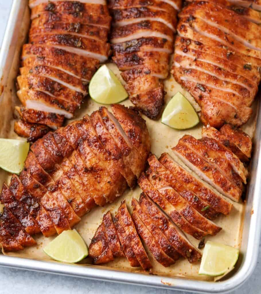 sliced chicken breasts on a parchment lined sheet pan