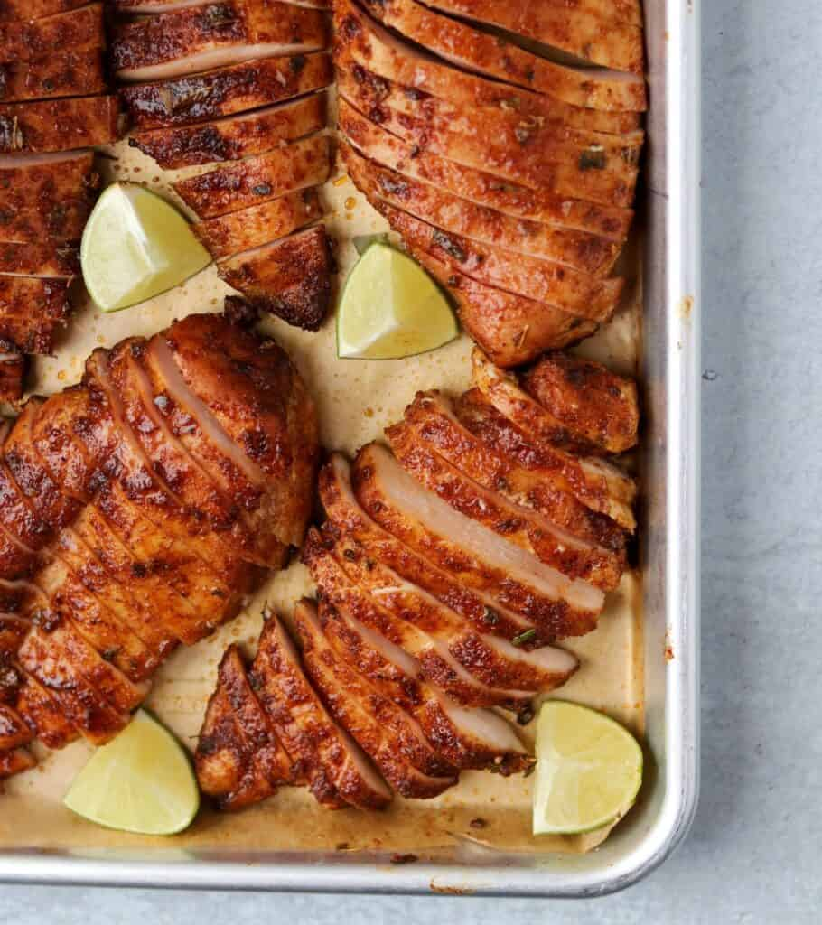 sliced smoked chicken breast on a parchment lined sheet pan with lime wedges