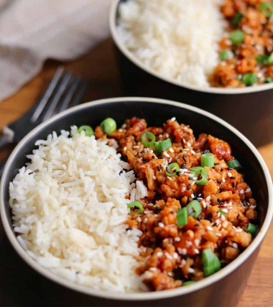 firecracker ground chicken topped with green onion and sesame seeds in a bowl with rice
