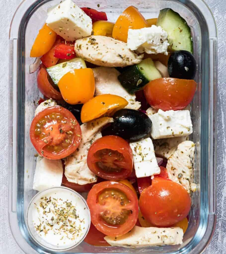 meal prep container with Greek chicken, tomatoes, olives, and feta